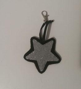 Hohtava laukkukoru tähti hopea-musta